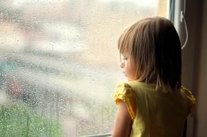 SINDROME DE TOURETTE Niña mirando por la ventana triste